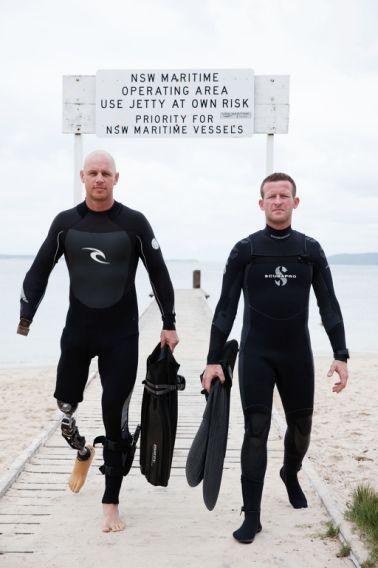 Paul De Gelder and Andy Casagrande walking down a boardwalk holding their flippers on a beach in Australia.